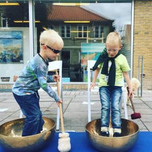 To nysgerrige drenge på 6 og 7 år, der leger med kæmpeklangskålene.
